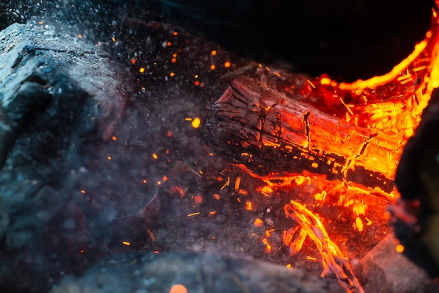 Smoldered logs burned in vivid fire close up. atmospheric  with flame of campfire. unimaginable detailed image of bonfire from inside with copyspace. whirlwind of smoke and glowing embers. Premium Photo