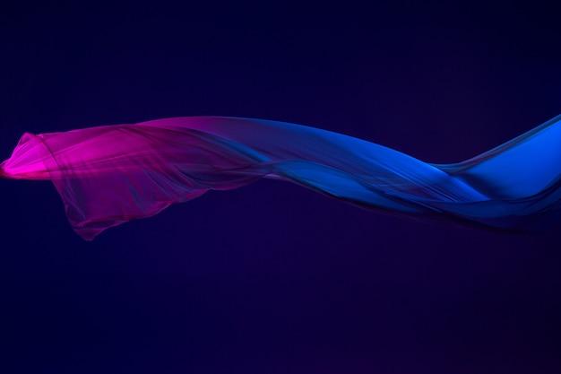 Гладкая элегантная прозрачная синяя ткань разделена на синем фоне. Бесплатные Фотографии