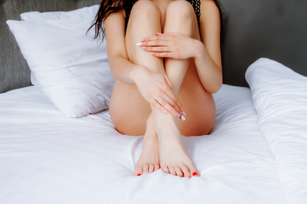 Smooth female legs in bed. women's legs after laser hair removal. Premium Photo