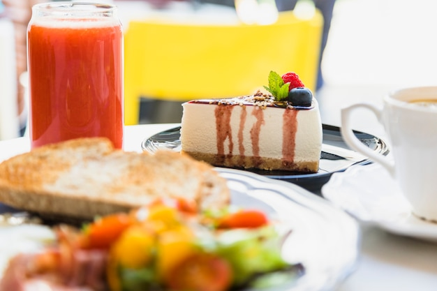 Smoothie; berry cheesecake and breakfast on table Free Photo