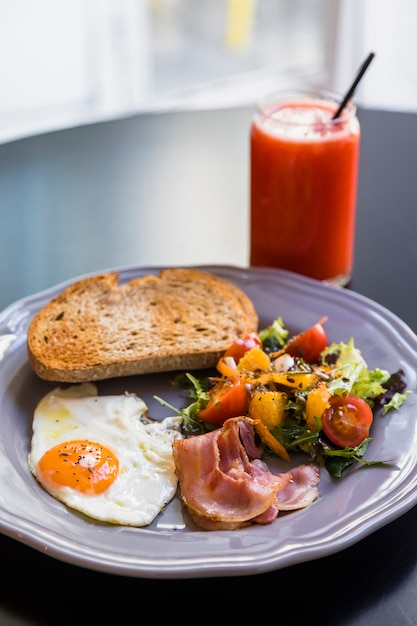 Smoothie in glass jar; toast; bacon; fried egg; salad on gray plate over the black table Free Photo