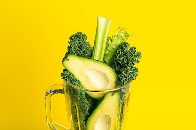 Smoothie recipe. green smoothie of vegetables (avocado, celery, cale salad, spinach) in a blender on a yellow background. vegan and healthy food detox concept Premium Photo