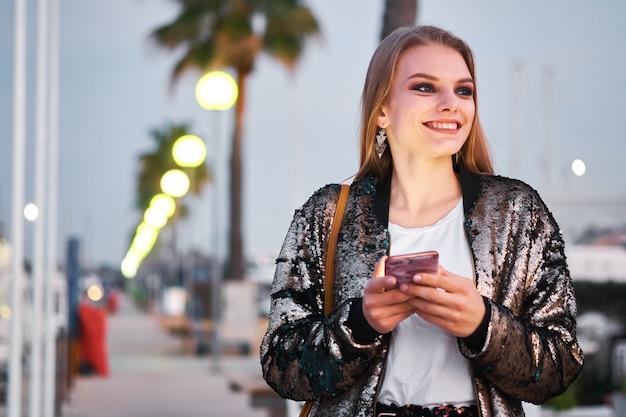 歩くとsmsメッセージを書く若い美しいブロンドの女性 Premium写真