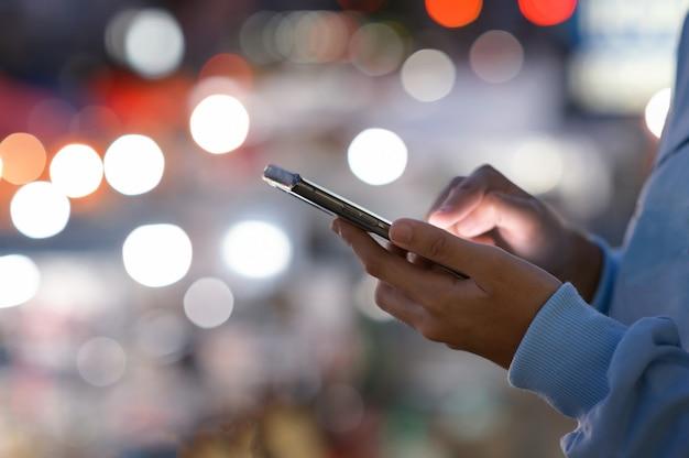市内の商店街、検索またはソーシャルネットワークの概念、流行に敏感な男が彼の友人にsmsメッセージを入力して夜にスマートフォンを使用して女性の手のクローズアップ画像 Premium写真
