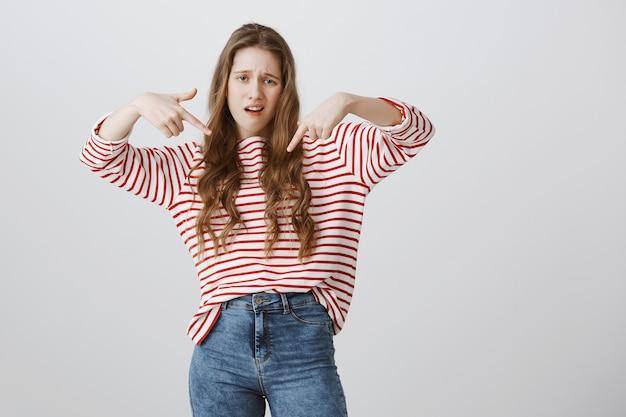 Самодовольная и крутая девушка указывает пальцем вниз, выпендривается Бесплатные Фотографии