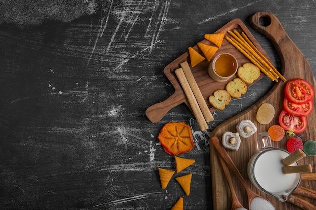 チップ、クラッカー、木製の大皿にペストリーのスナックボード 無料写真