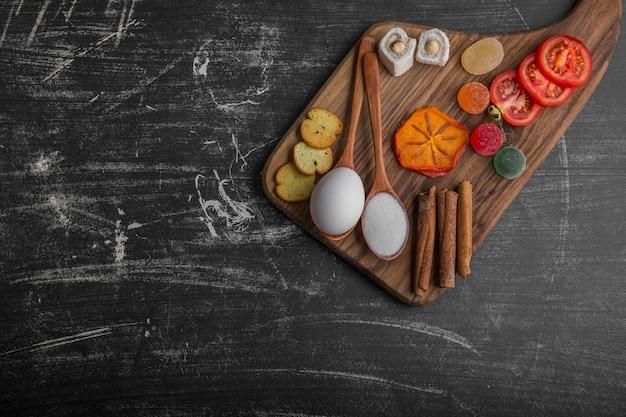 上の隅に卵、トマト、ペストリーが入ったスナックボード 無料写真