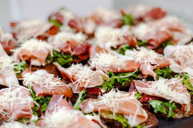 Snack plate at the event: prosciutto sandwiches, sun-dried tomatoes, fresh lettuce and grated cheese. Premium Photo