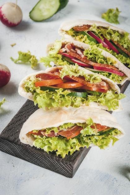 Snack. takeaway food, street fast food. pita bread sandwich with fresh vegetables lettuce, cucumber, tomato, radish, beef meat Premium Photo