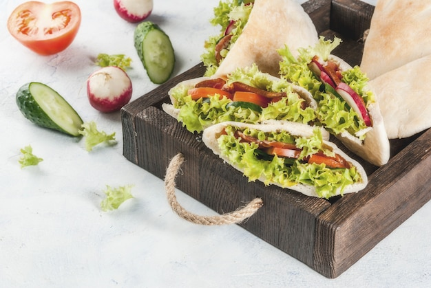 Snack. takeaway food, street fast food. pita bread sandwich with fresh vegetables lettuce, cucumber, tomato, radish, beef meat Premium Photo
