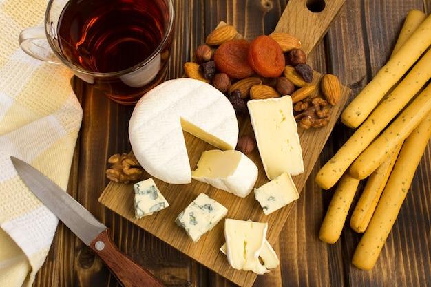 茶色の木の背景にチーズとブレッドスティックのスナック。上からの眺め。 Premium写真