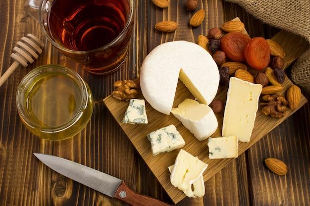 木製のまな板の上にチーズ、お茶、蜂蜜とスナック。上からの眺め。 Premium写真