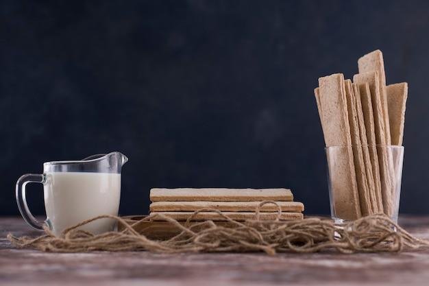 Закуски и крекеры в деревянном блюде с стаканом молока на черном фоне. Бесплатные Фотографии
