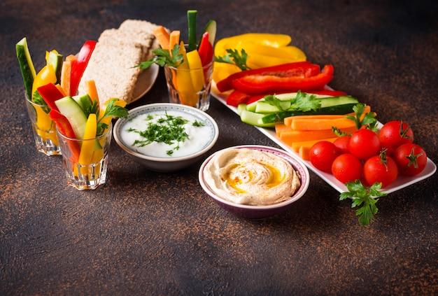 Snacks bar. vegetables sticks and hummus Premium Photo