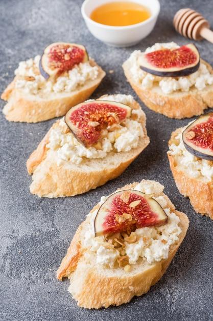 Snacks bruschetta with cottage cheese, walnut and honey and figs Premium Photo