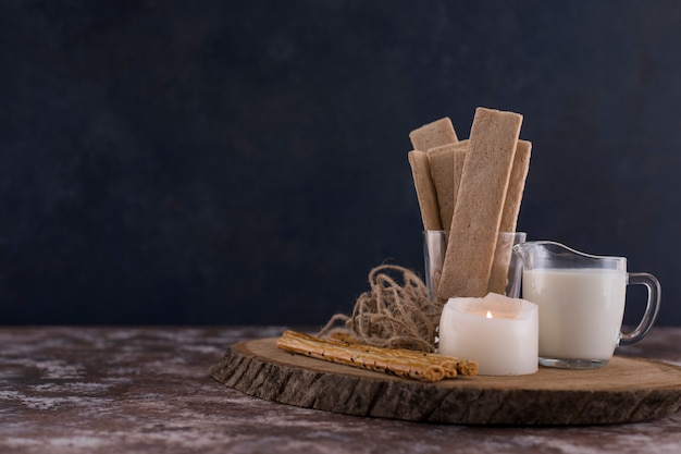 Snacks and crackers with a glass of milk on a wooden board with a white candle aside. Free Photo