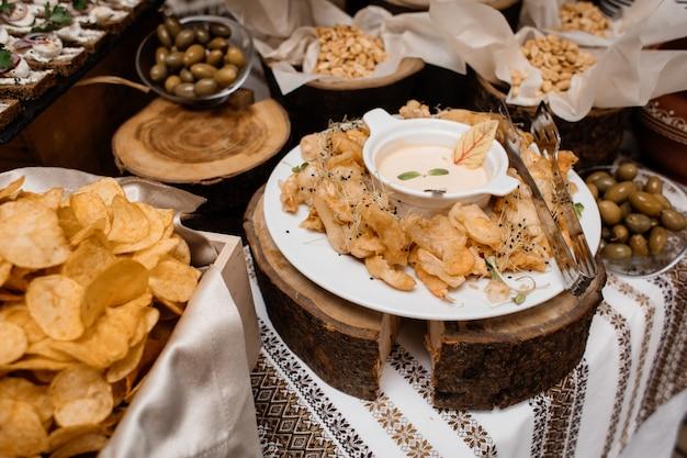 Закуски, такие как чипсы, оливки и орехи на столике Бесплатные Фотографии