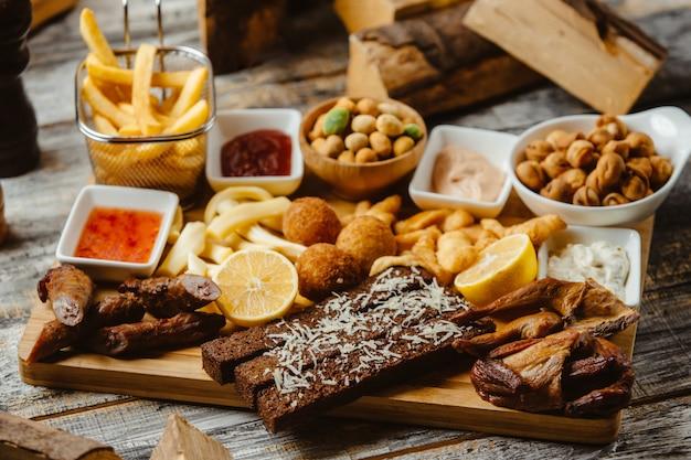 Закуски с копчеными крылышками колбаски картофель фри орехи и соусы Бесплатные Фотографии