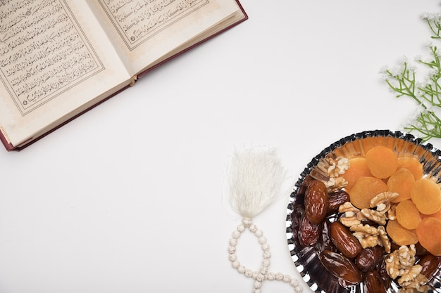 Snacks and quran on table Free Photo