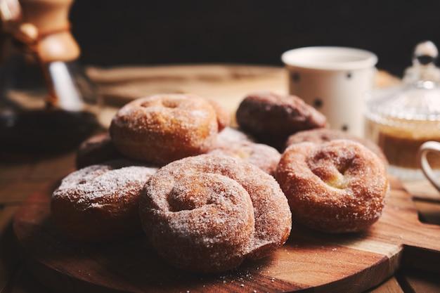 Змеиные пончики с сахарной пудрой и кофе химекс на деревянном столе Бесплатные Фотографии