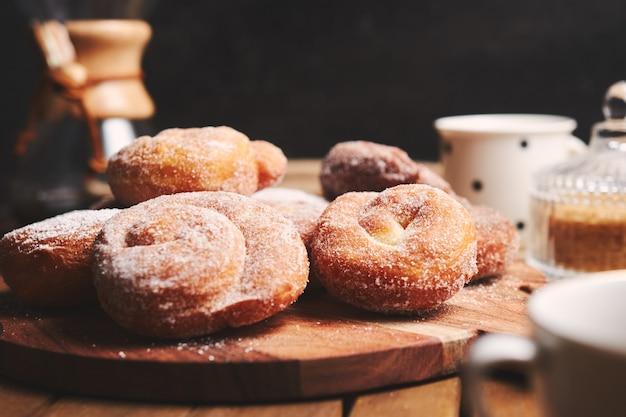 Ciambelle di serpente con zucchero a velo e caffè chemex su un tavolo di legno Foto Gratuite