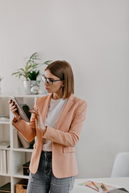 白いオフィスで働く短髪の女性のスナップポートレート。ピンクのジャケットと白いtシャツを着た女性は思慮深くタブレットに見えます。 無料写真