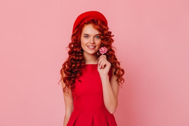 우아한 드레스와 롤리팝을 들고 웃 고 세련 된 모자에 파란 눈 생강 아가씨의 스냅 숏. 무료 사진