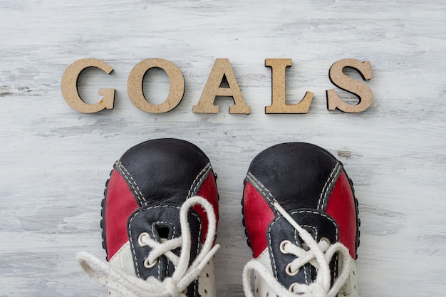Sneakers on light surface in front of the word goals Premium Photo