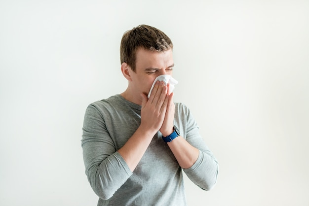 Sneezing man in handkerchief blowing wiping running nose isolated on white background, coronavirus and flusymptoms, respiratory contagious symptoms Premium Photo