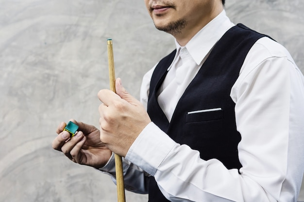 Snooker player standing waiting hold his cue stick and chalk Free Photo