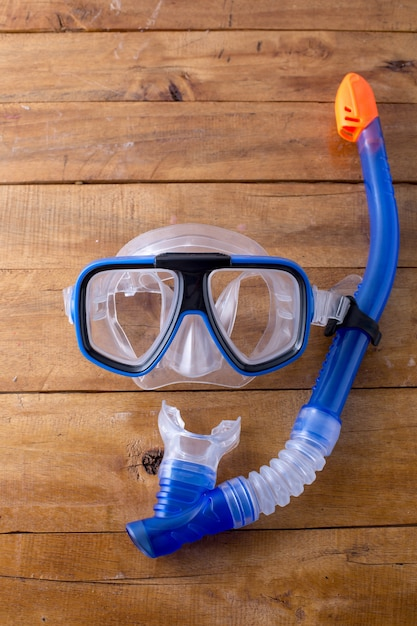 Snorkel and fin on wooden background Premium Photo