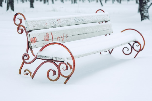 Snow-covered bench with heart symbol in the city park Premium Photo