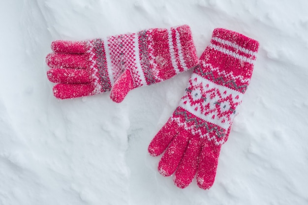 Snow covered gloves on snow, winter background. Premium Photo