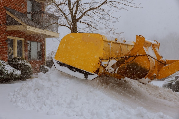 Snow remover truck cleaning city streets in snow storm Premium Photo