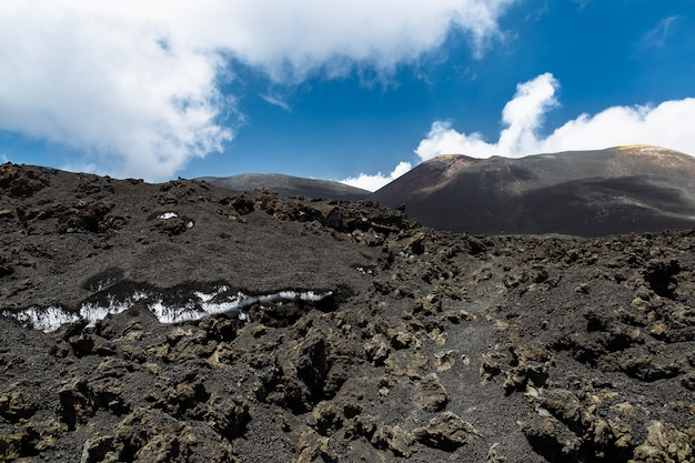 Snow under volcanic ash on top of the volcano etna in sicily, italy Free Photo