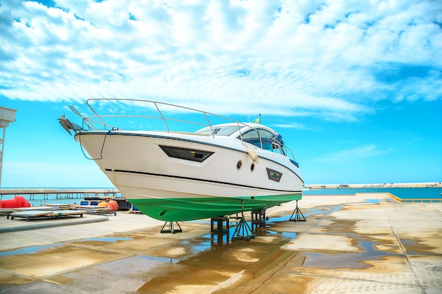 A snow white yacht stands on a pier on coasters on a sunny day against a beautiful sky with clouds Premium Photo