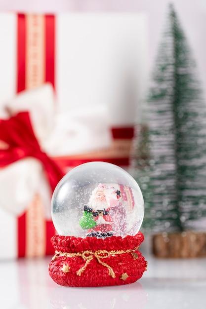 サンタクロースとクリスマスの装飾が施された雪玉 無料写真