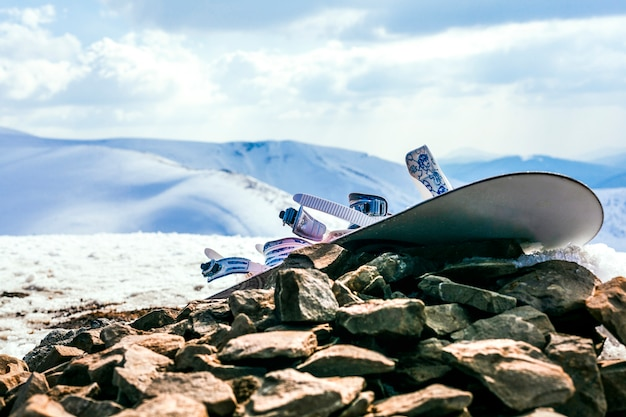 Snowboard with bindings on rocks over the snowy mountain landscape Free Photo