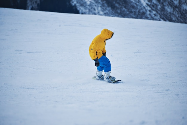 Snowboarder in bright yellow parka and blue pants looks down on snow slope before start to ride at sunny winer day in mountain ski resort Free Photo