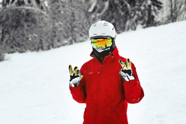 Snowboarder in red jacket, white helmet and yellow glasses poses on the hill  Free Photo