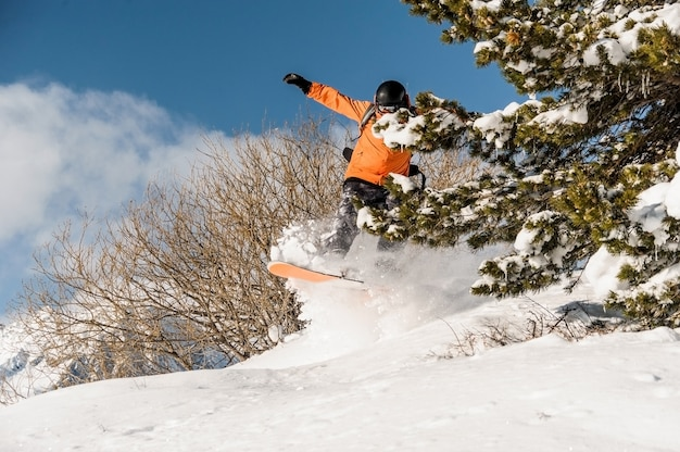 Snowboarder in orange sportswear jumping on the powder mountain slope Premium Photo