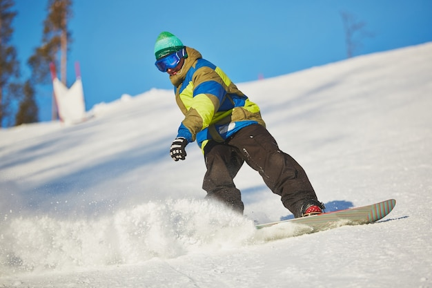 Snowboarder sliding from the mountain in winter day Free Photo