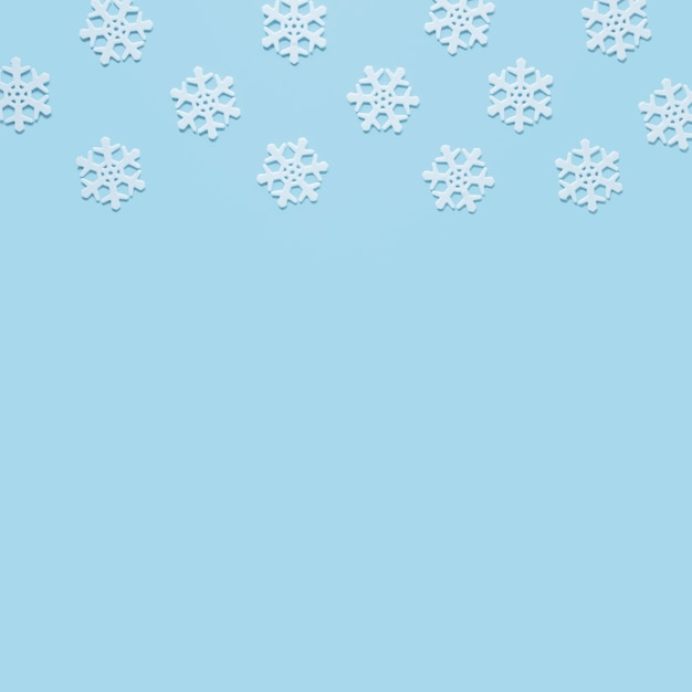 Snowflake on baby blue background with copy space Free Photo