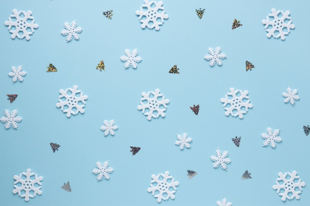 Snowflakes and christmas trees on blue background Free Photo