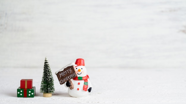 Snowman doll, mini christmas tree and gift boxes Premium Photo