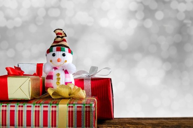 Snowman And Gift Boxes On Wooden Table Front Of Winter Background