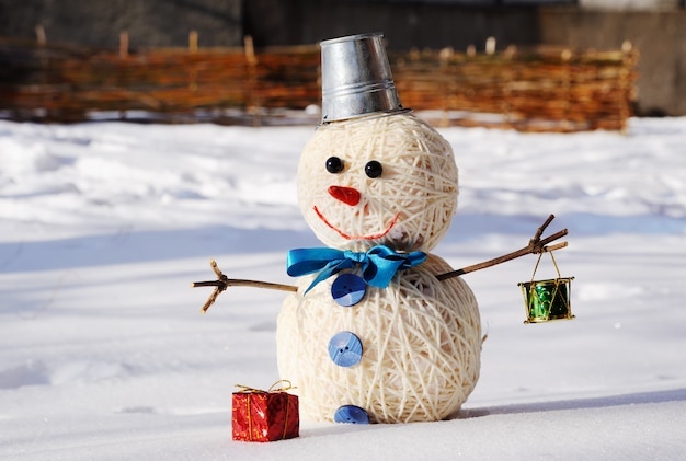 Snowman with a bucket on his head on a background of snow Premium Photo
