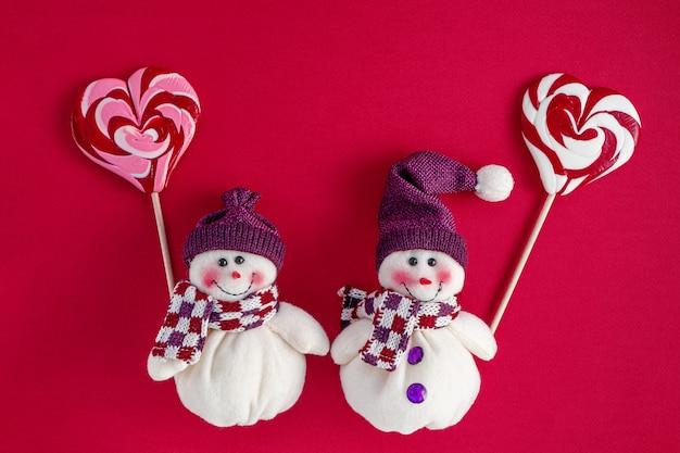 Снеговики держат традиционные рождественские конфеты в форме сердца Premium Фотографии