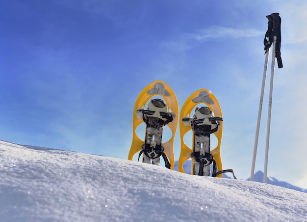 Snowshoes planting in the snow in mountain under blue sky Premium Photo