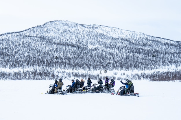 Snowy day with people riding the snowmobiles and a mountain in the distance in the north of sweden Free Photo